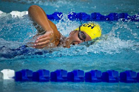 шапка за плуване в жълто в коридор в басейн